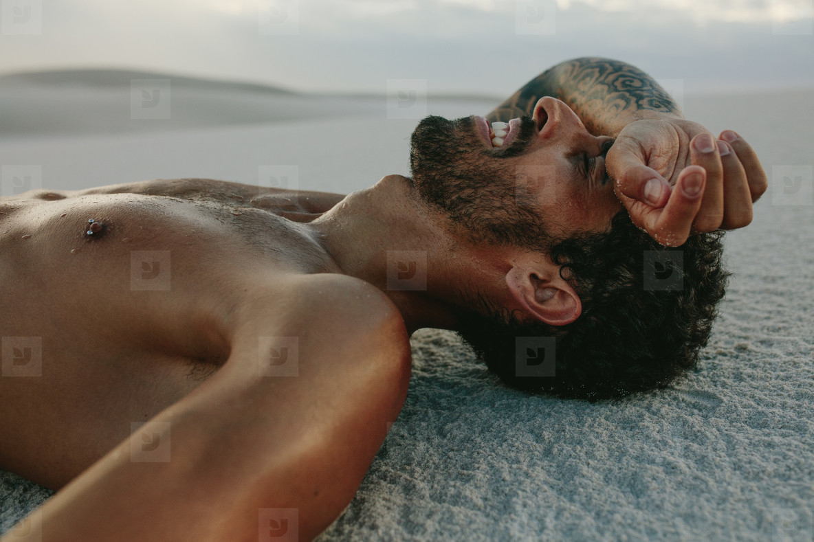 Tired man resting on sand after intense workout