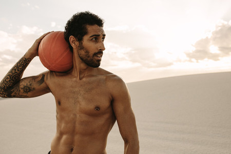 Muscular man with a exercise ball in desert