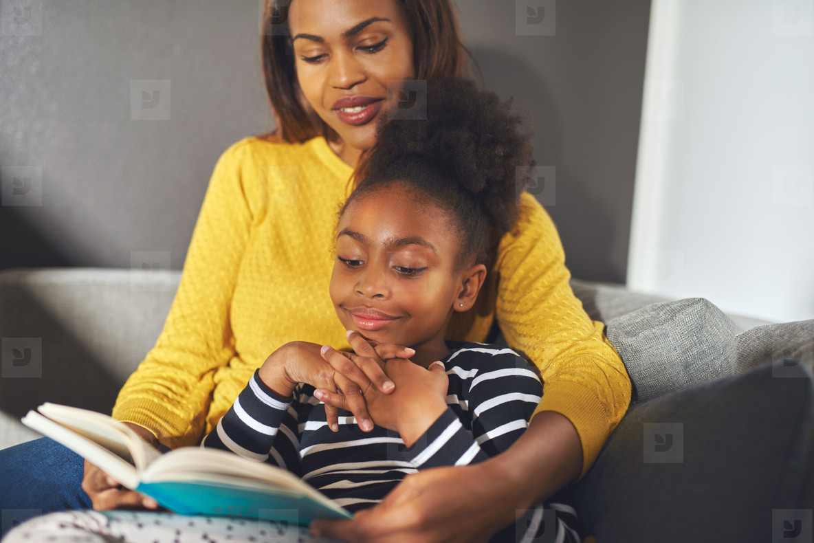 Black mom and daughter reading a book