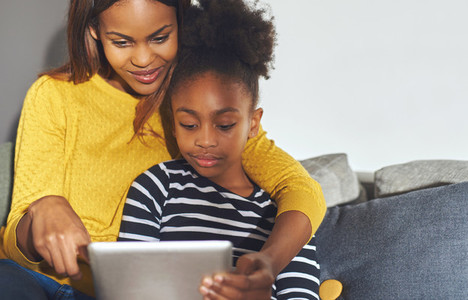 Black mom and daughter learning on tablet