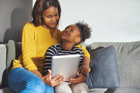 Black mom and daughter with tablet