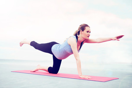 Young pregnant woman practicing pilates