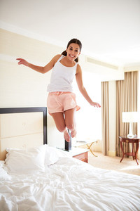 Woman jumping on bed wearing pajamas