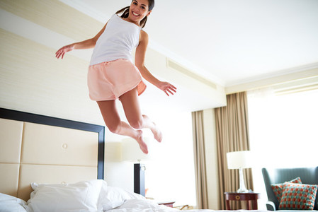 Angled view of woman jumping on bed