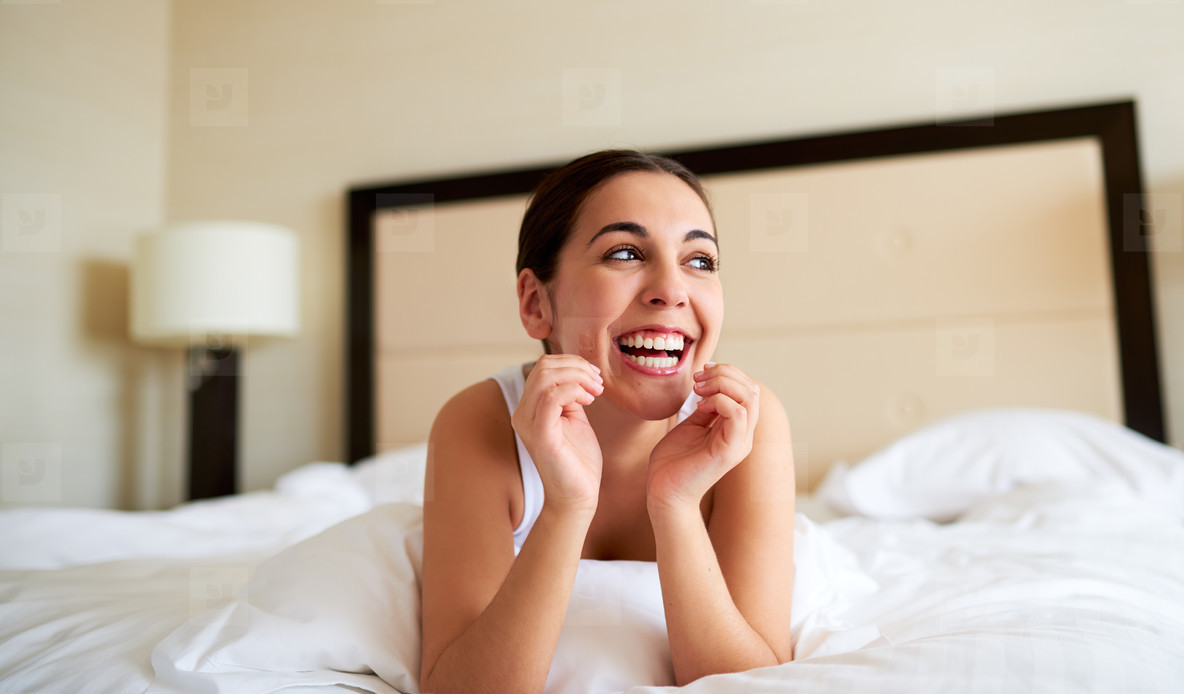 Woman lying down in bed and smiling