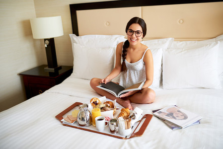 Woman relaxing in bed looking up smiling