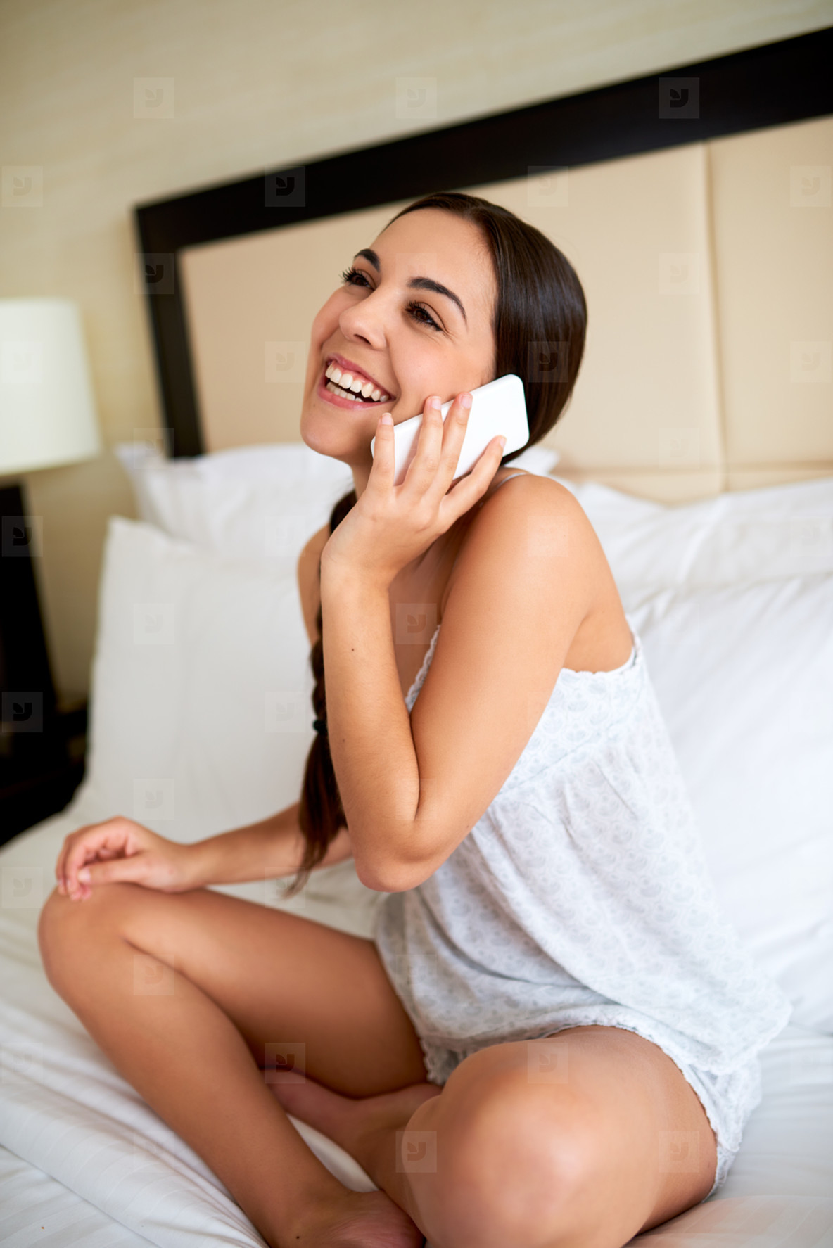 Young woman on cell phone in bed