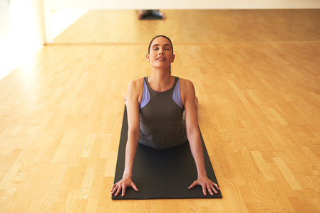 Thoughtful Young Woman Stretching on Yoga Mat