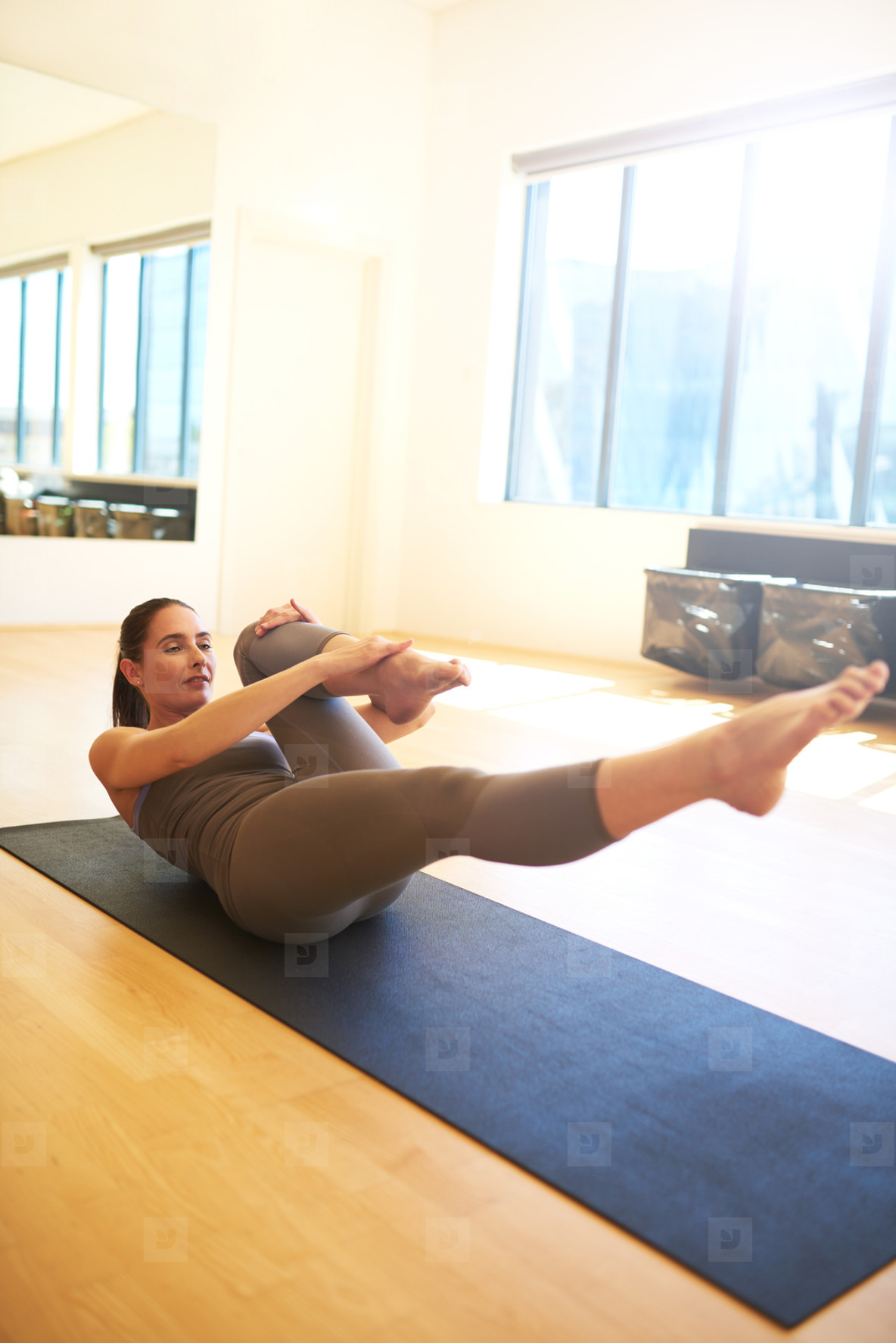 Woman Practicing Pilates on Floor Mat in Studio