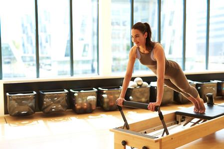 Brunette Woman Practicing Pilates in Studio