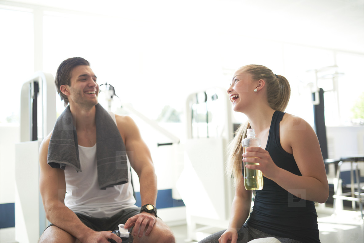 Healthy Couple Relaxing After Workout In the Gym