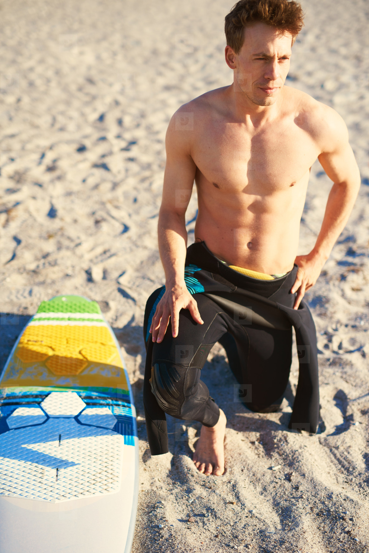 Handsome muscular surfer kneeling with his board