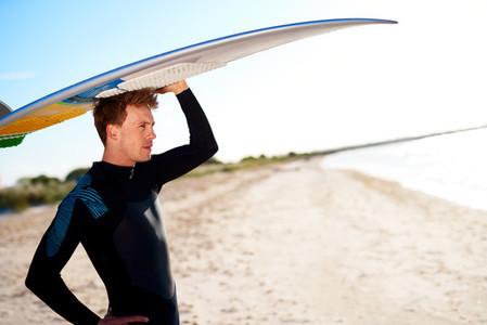 Attractive surfer balancing his board on his head