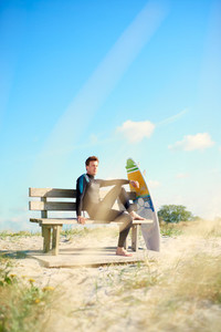 Surfer relaxing on a wooden bench with his board