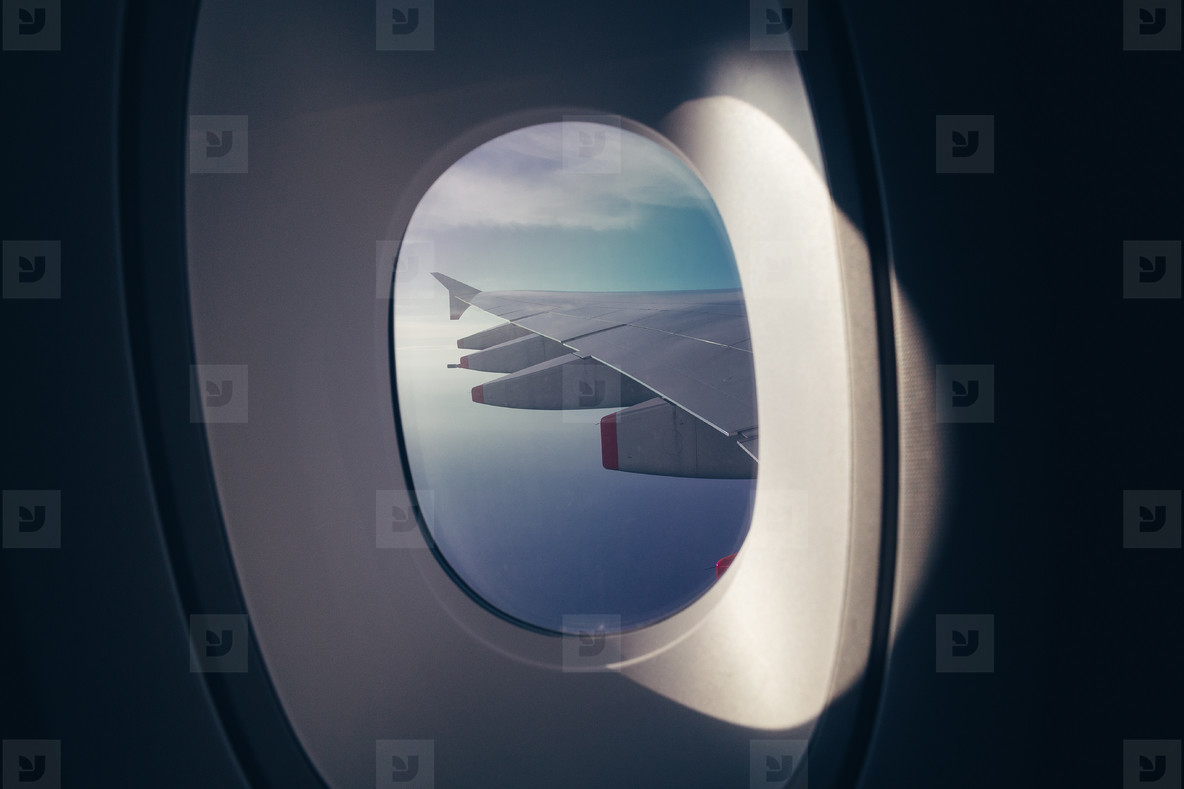 Looking at wing and sky through airplane window