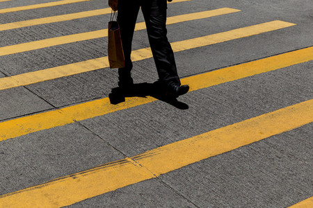Businessman wearing suit with shopping bag crossing road in Hong