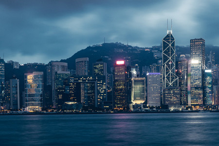 Hong Kong skyline on Victoria Harbour with moody gray sky and cl