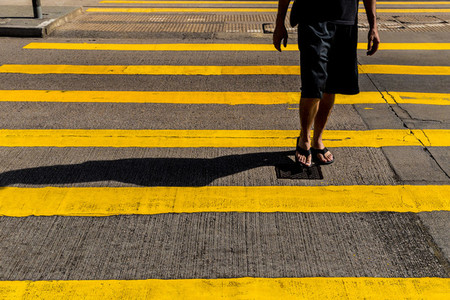 Tourist man in shorts and sandals crossing road in Hong Kong