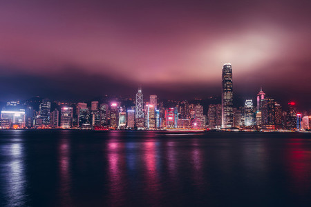 Hong Kong skyline on Victoria Harbour with moody mist and clouds