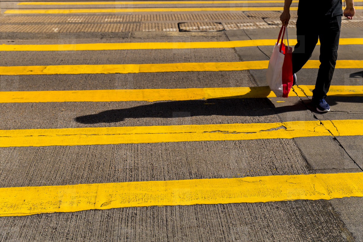 Adult man crossing road holding shopping bag in Hong Kong