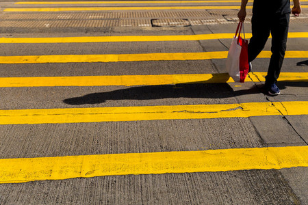 Adult man crossing road holding shopping bag in Hong Kong