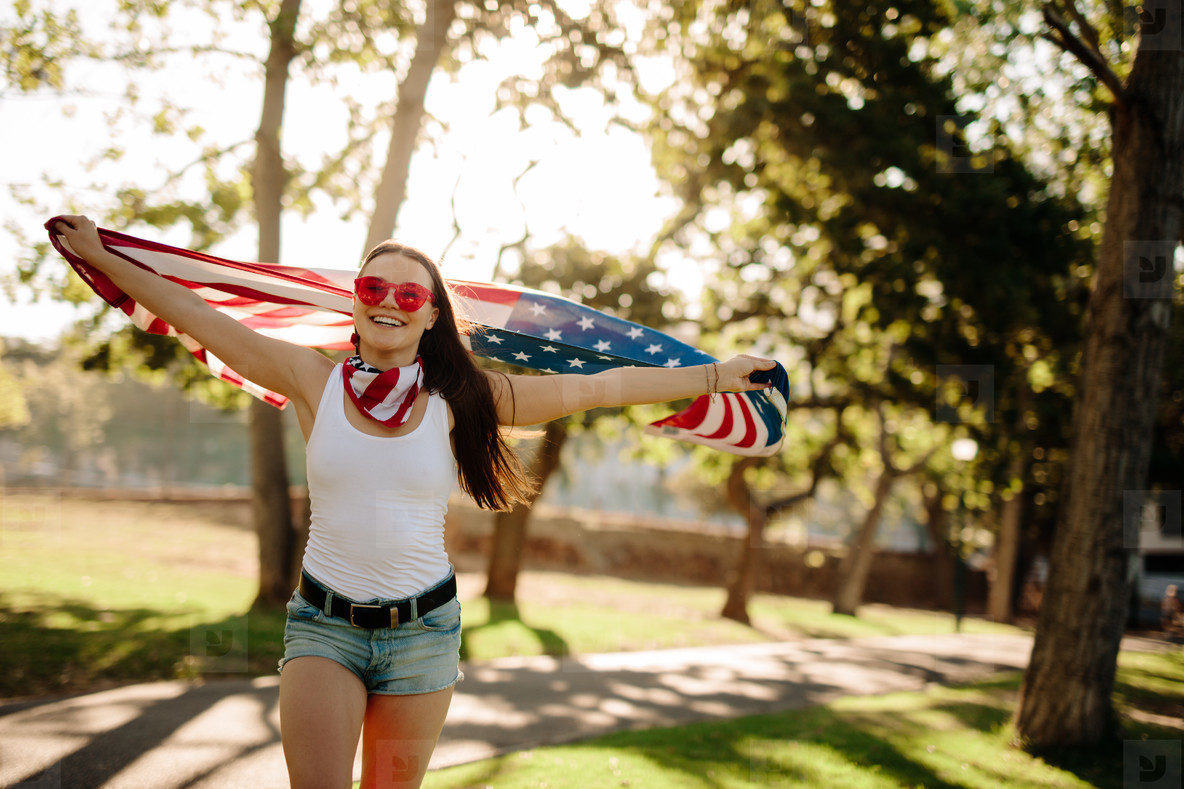 American woman celebrating independence day at park