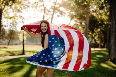 Patriotic girl with american flag in the park