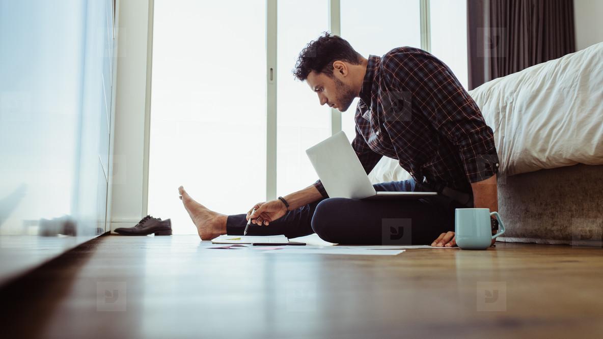 Man working on laptop sitting at home