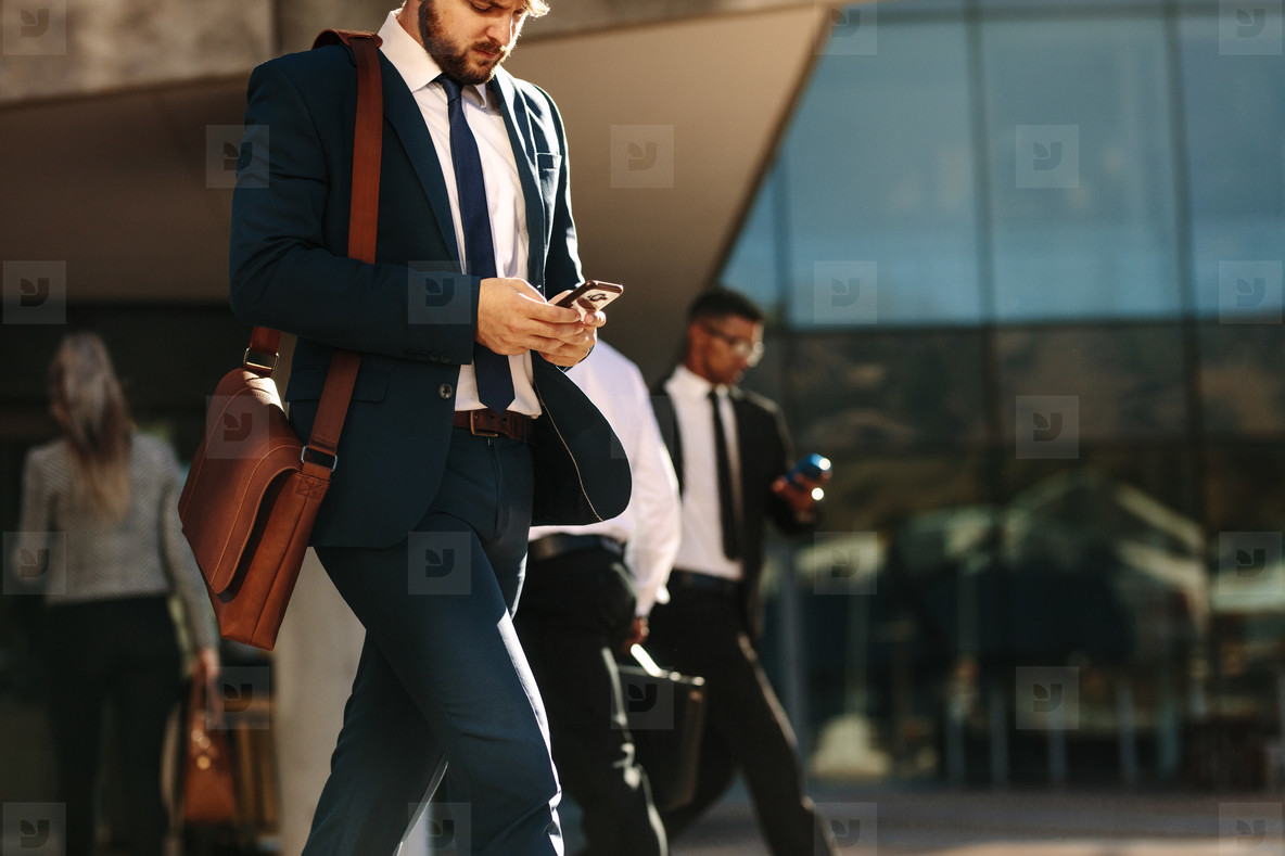 Business people using mobile phone while walking on street to of