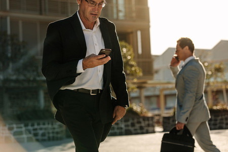 Men using mobile phone while commuting to office