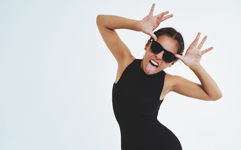 Impudent cheeky young woman sticking out a tongue