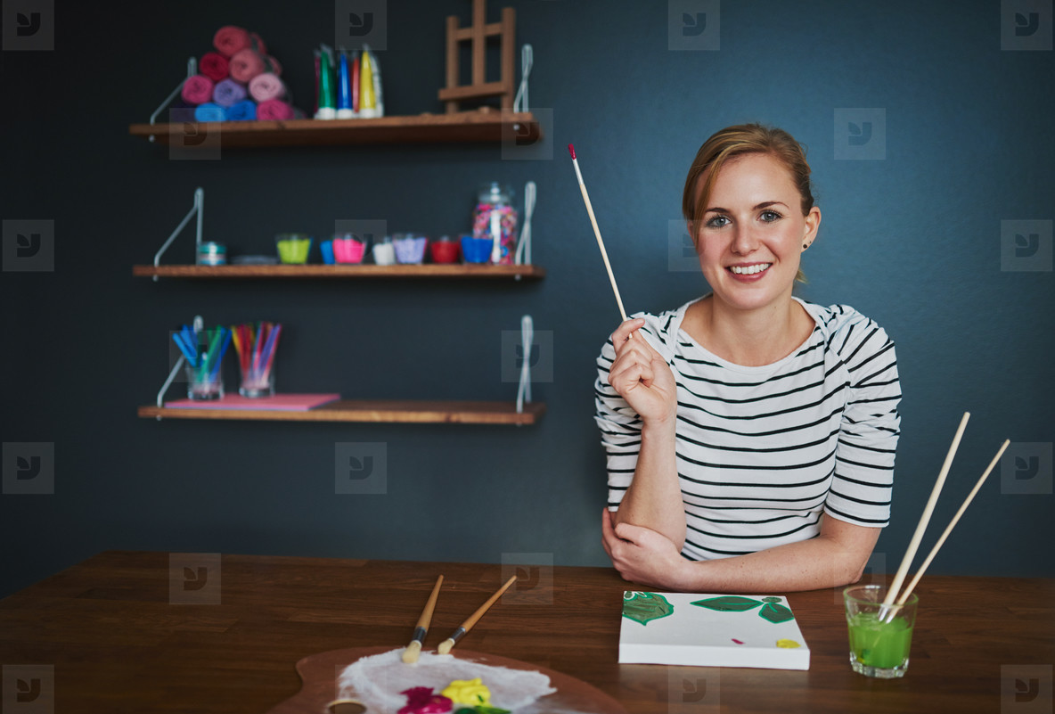 creative woman smiling at camera while painting