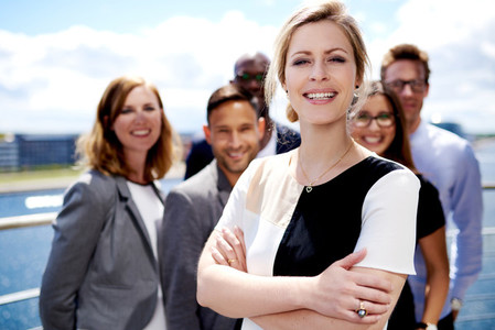 White female executive standing in front of colleagues