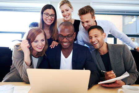 Group of executives gathered around laptop