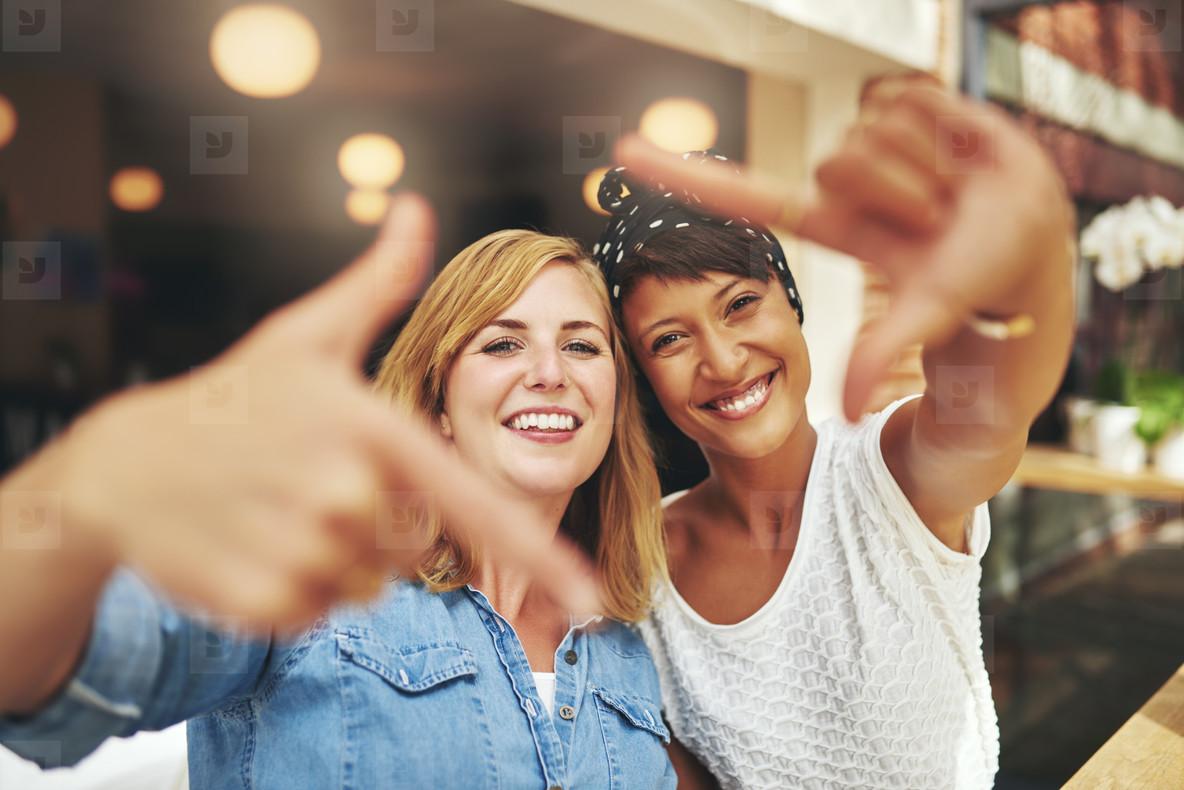 Vivacious young women framing their faces