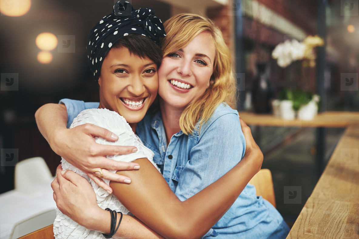 Two happy affectionate young woman hugging