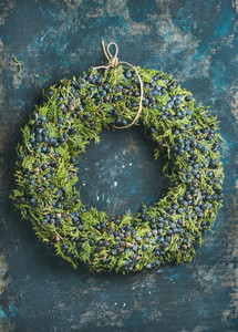 Christmas decorative wreath over dark blue plywood wall background