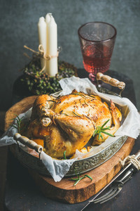 Christmas table set with oven roasted whole chicken and wine