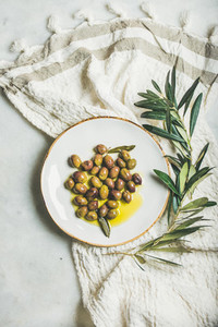 Pickled green olives in olive oil on white ceramic plate