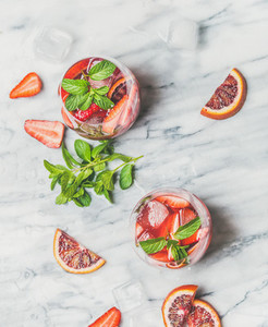 Orange and strawberry summer Sangria in glasses grey marble background
