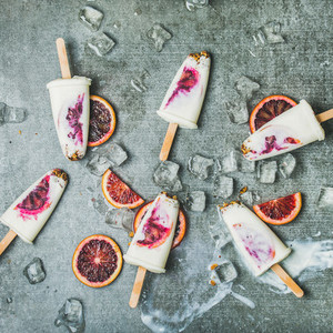 Blood orange  yogurt  granola popsicles on ice cubes  square crop