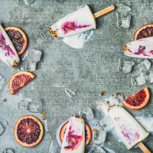 Orange yogurt granola popsicles on ice cubes square crop