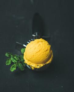 Mango sorbet ice cream scoop in scooper over black background