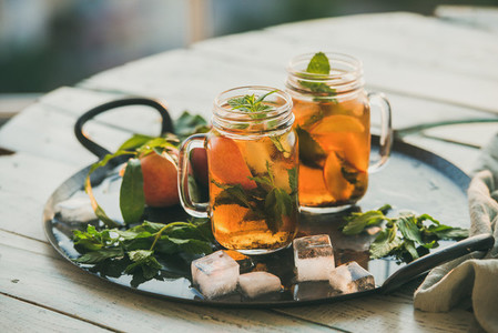 Summer refreshing cold peach ice tea on wooden table