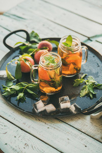 Summer refreshing cold peach ice tea on tray  copy space