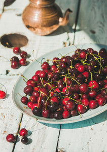 Plate of sweet cherries on light blue wooden table background
