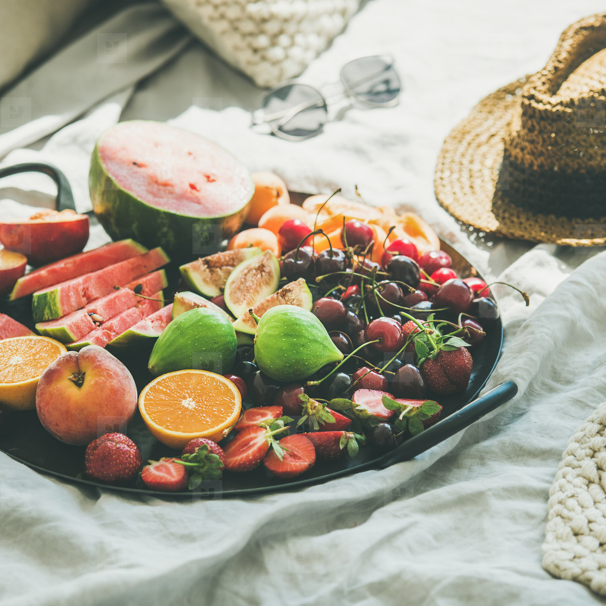 Tray full of fruit over light blanket background  square crop