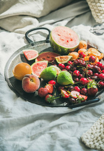 Tray full of fruit over light blanket background copy space