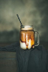 Iced caramel macciato coffee with milk in jar copy space