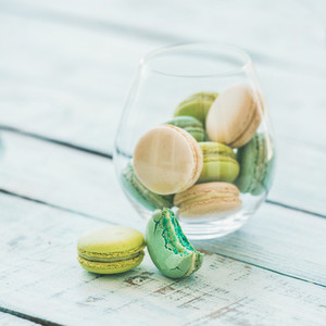 Colorful pastel French macaron biscuits in glass on wooden table